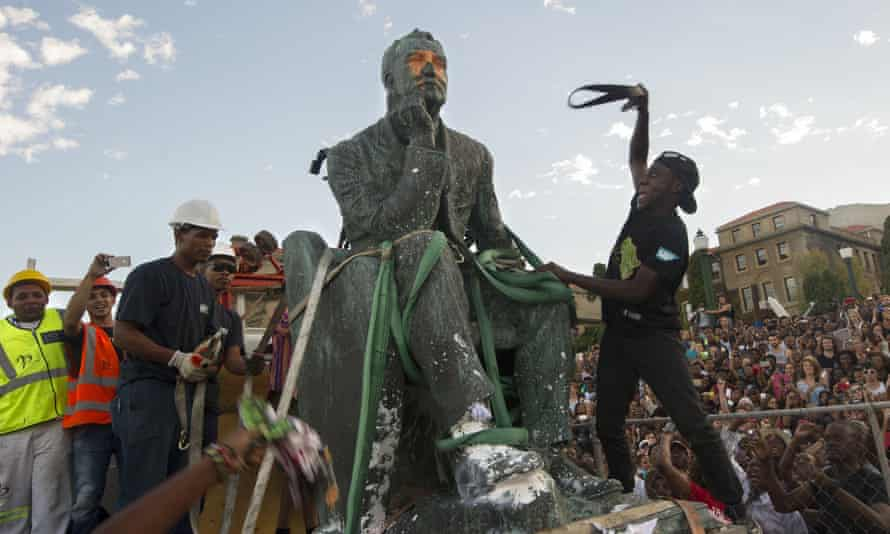 Students attack the defaced University of Cape Town statue of Cecil Rhodes as it is removed after a month of student demonstrations.