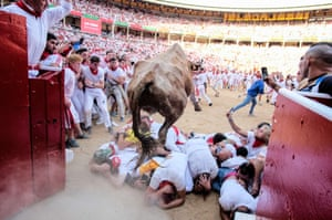 Revellers crouch in front of a leaping bull as the bulls run into the arena