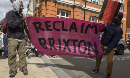 Two men hold a banner with the words Reclaim Brixton