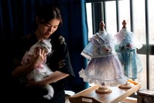 Changsha, China: Wu Qiuqiao dresses her cat Liu Liu at her house