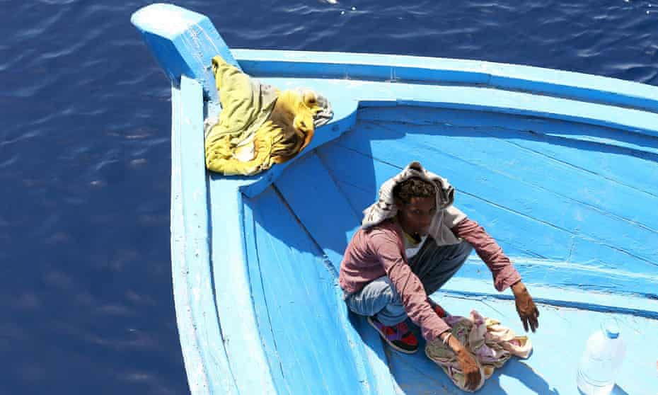A boy, part of group of 300 sub-Saharan African migrants, sits in a boat during an Italian rescue operation.