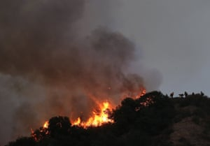 Firefighters work to contain the Bobcat Fire burning on a hillside on Tuesday in Monrovia, California.