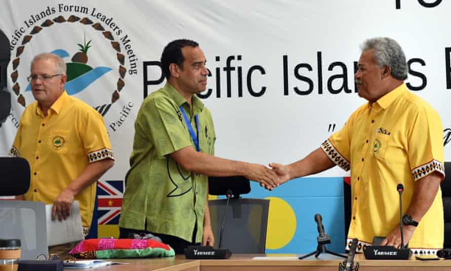 Scott Morrison walks away as Vanuatu's Minister for Foreign Affairs Ralph Regenvanu (C) and Tuvalu's Prime Minister Enele Sopoaga shake hands after a press conference during the Pacific Islands Forum in Funafuti, Tuvalu.