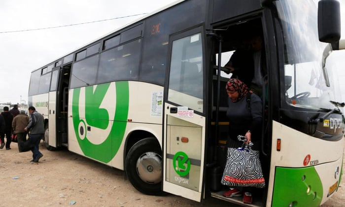 A woman disembarks a Palestinians-only bus before crossing through Israel's Eyal checkpoint.