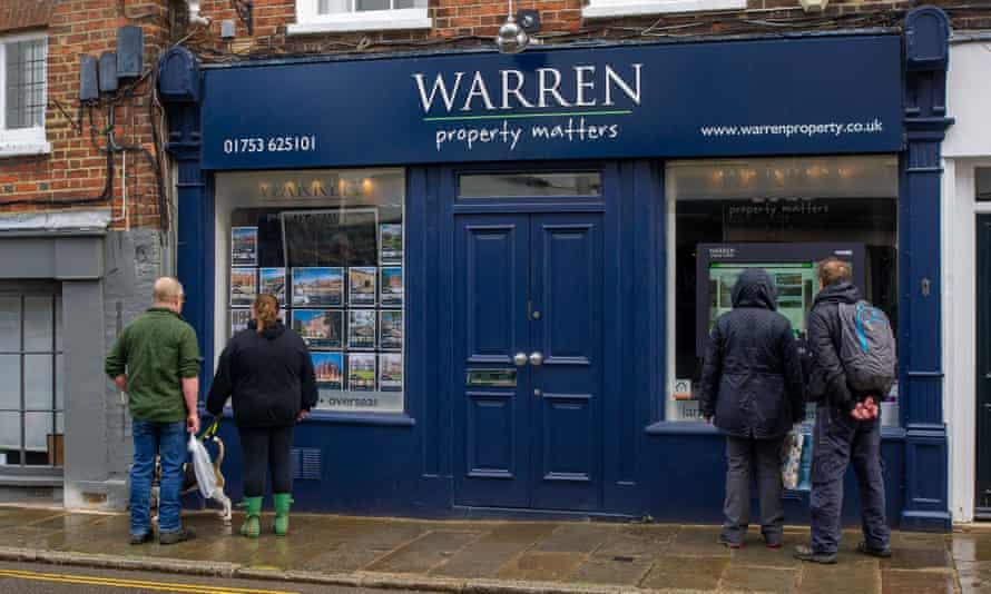 People look at properties in an estate agent's window in Eton, Windsor, England.