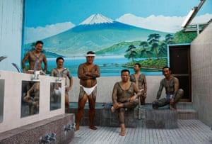 Tattoo artist Asakusa Horikazu poses for a photograph with clients at a public bath in Tokyo.