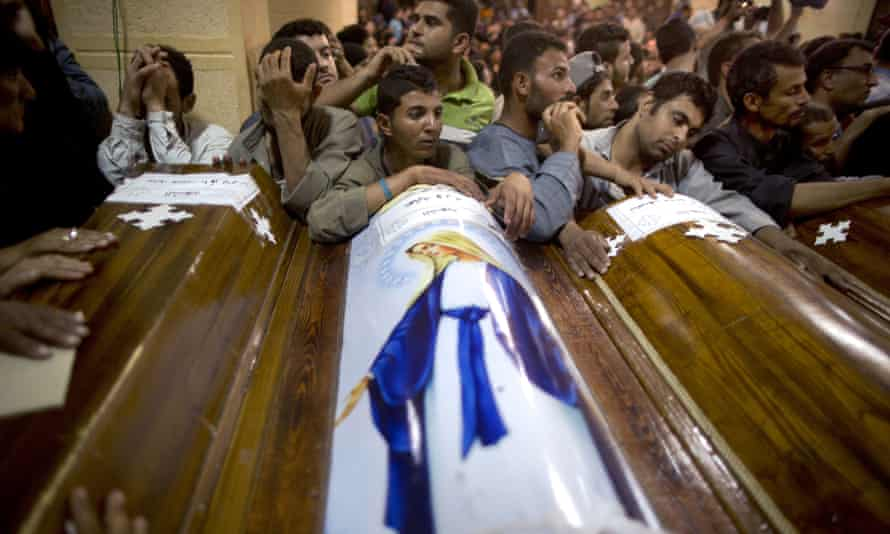 Relatives of Coptic Christians who were killed during a bus attack, surround their coffins, during their funeral service, at Abu Garnous Cathedral in Minya, Egypt.