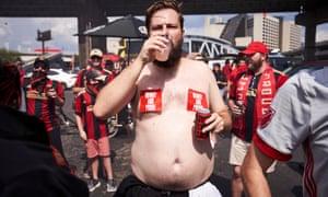 Jam Henson, a shirtless Atlanta United fan drinking beer.