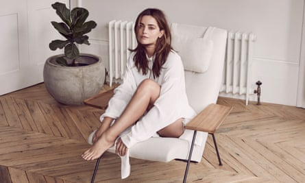 Jenna Coleman in a white shirt, sitting on a white chair on a wooden floor