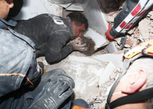 Rescue workers surround a girl rescued from the rubble of a collapsed building in İzmir, Turkey
