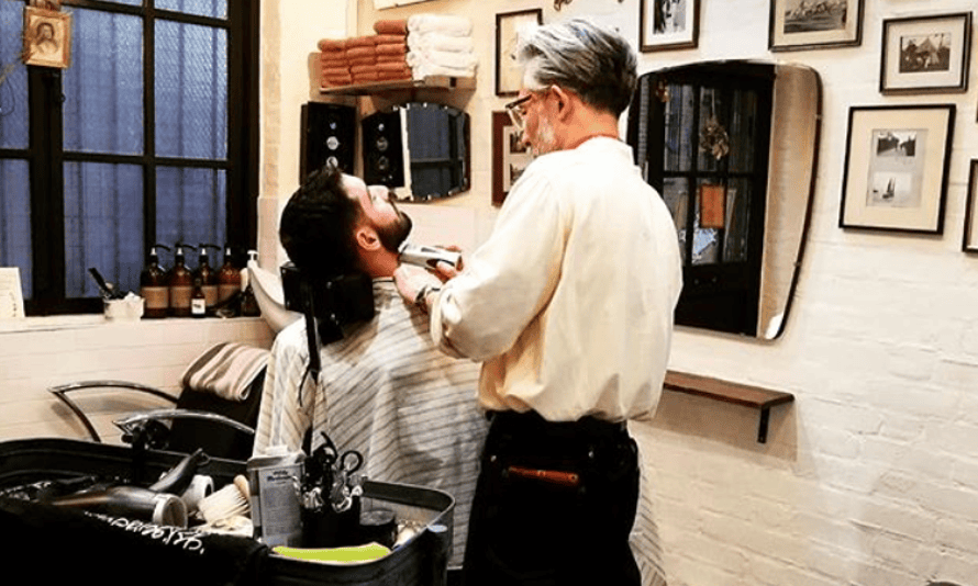 A man having his beard trimmed in a barber's