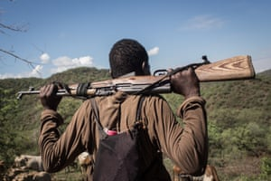 A Tungen herder watches over his livestock with an illegal rifle near the Arabal riverin Baringo County, Kenya