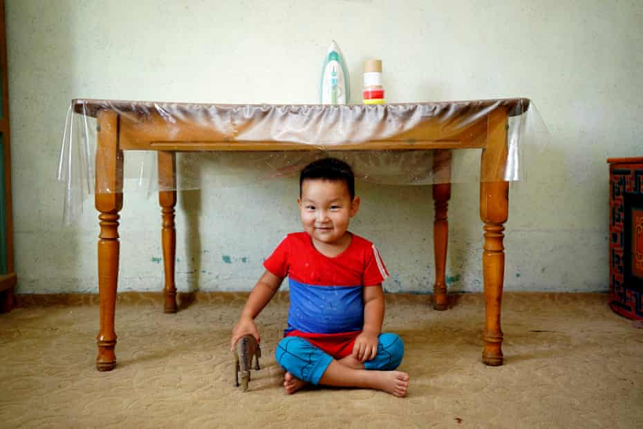 A boy plays with his toy horse at home, surrounded by traditional Mongolian items, in Khanbogd