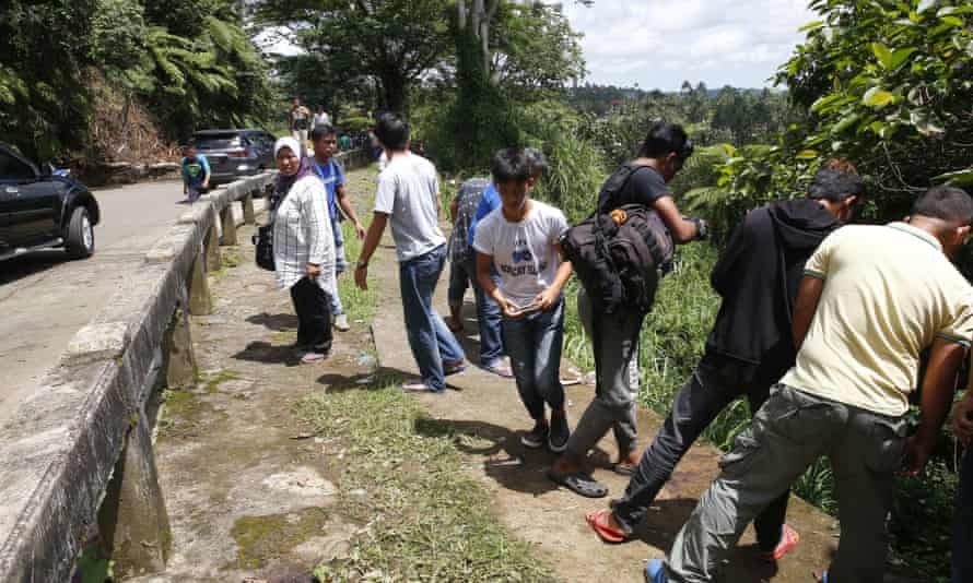 Onlookers take photos of the bodies of eight men found shot dead in Marawi.