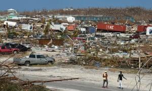 Men walk past damage in the wake of Hurricane Dorian in Marsh Harbour, Great Abaco, Bahamas.