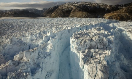 A large crevasse forms in the Helheim glacier in Greenland, as it collapses in to the sea.