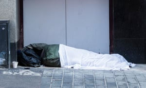 A homeless person sleeps in a shopfront in the centre of Birmingham.