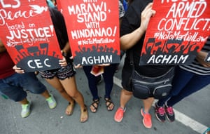 Protesters hold anti-martial law signs during a large demonstration held on Thursday at Mendiola Bridge in Manila