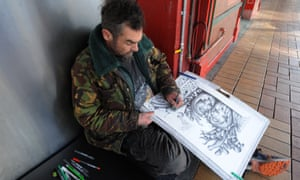A homeless man draws a picture on a street in Wellington.