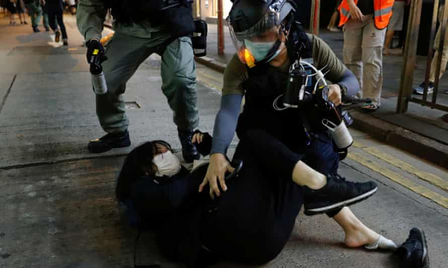 Riot police detain a pro-democracy demonstrator in Hong Kong
