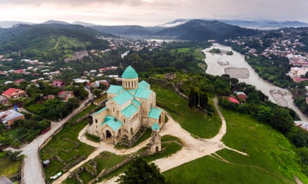 Aerial view of Bagrati Cathedral in Kutaisi, at the top of a hill, with a view sloping down into a valley with houses and a river