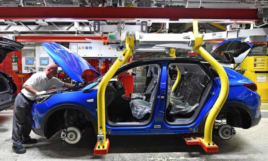 A man works on the assembling of an Opel Grandland X SUV car
