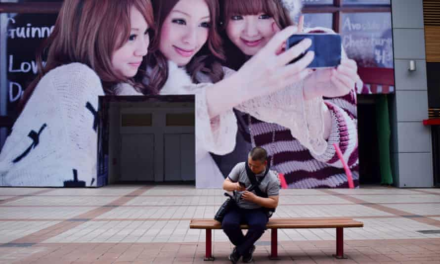 A man looks at his mobile phone in front of a huge poster in Beijing