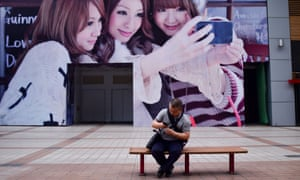 A man looks at his mobile phone in front of a billboard on a business street in Beijing