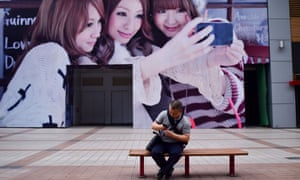 A man looks at his mobile phone in front of a huge poster along a business street in Beijing