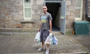 A man leaves a foodbank in Camborne, Cornwall, July 2017