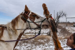 A Lakota boy places a sacred staff on a horse during a ride to meet Brad Upton, descendant of the commander of the Wounded Knee massacre on the Cheyenne River reservation in Eagle Butte.