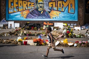 Carter Sims, 3, of Pine Island, Minn., runs past a mural at the George Floyd memorial outside Cup Foods, Thursday, June 25, 2020, in Minneapolis. Floyd, a Black handcuffed man, died May 25 after Derek Chauvin, a white officer, pressed his knee into Floyd's neck for nearly 8 minutes and held it there even after Floyd said he couldn't breathe and stopped moving. (Leila Navidi/Star Tribune via AP)