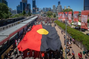 The Aboriginal flag is carried by a section of the crowd in Brisbane