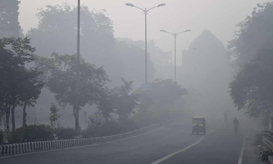 Indian commuters drive and cycle through air pollution in Delhi the day after Diwali.