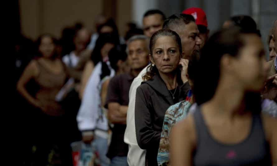 People stand in line outside a state-owned Bank of Venezuela to deposit their 100-bolivar notes.