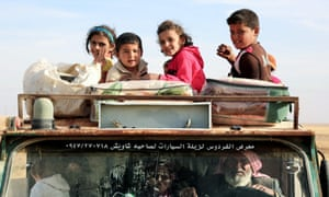 Syrian children smile from a pickup truck, as they come to safety after fleeing areas controlled by the jihadist group Islamic State