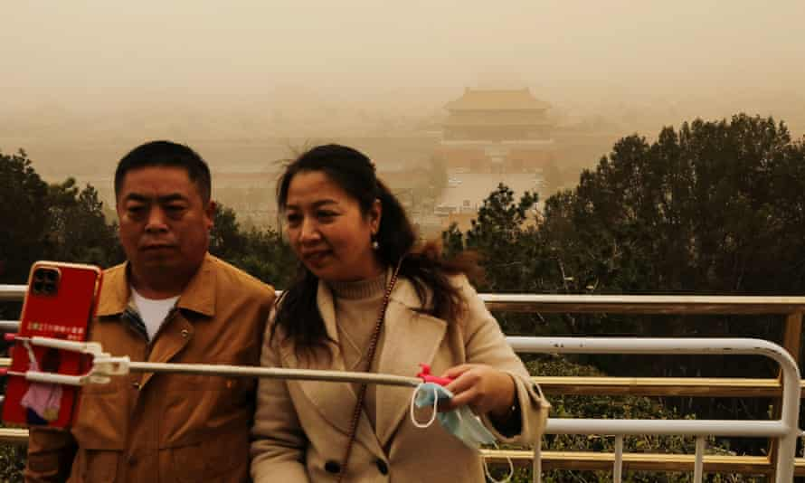 Visitors pose for a shot with the Forbidden City at Jingshan Park in the background.