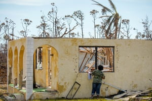 A woman looks through a broken window into a destroyed house in the High Rock community in the eastern side of Grand Bahama island.