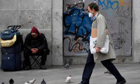 Man wearing  face mask walks down a high street in Spain