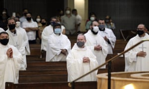 Priests attend an ordination ceremony in Texas, where an average of 3,200 people per day are being admitted to hospitals.