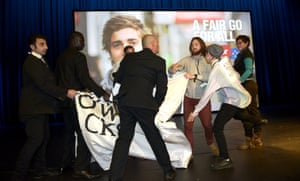 Protesters who interrupted Andrew Giles speech are escorted out by security.