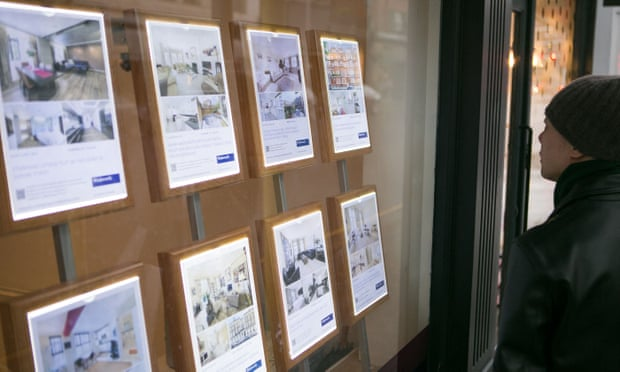 A young man looking at an estate agents window.
