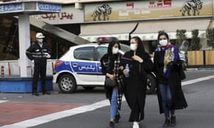 A police officer and pedestrians wear masks in central Tehran on Sunday