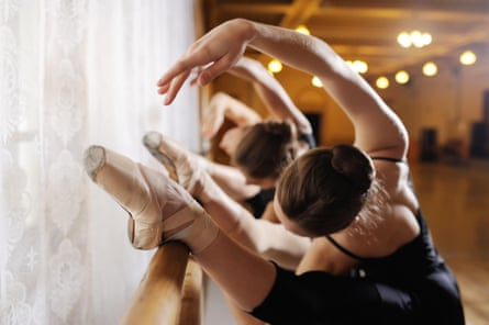 Three dancers performing on a ballet barre