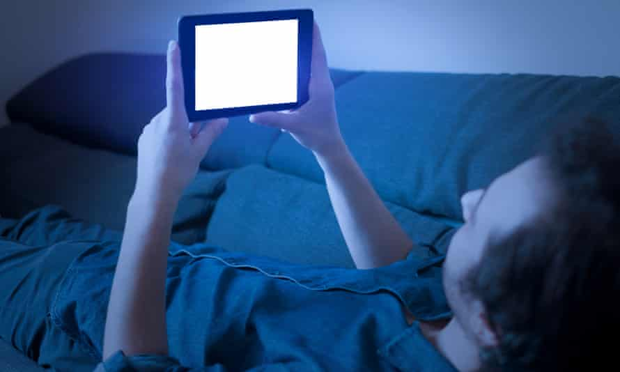 Man looking at blue light on a phone screen