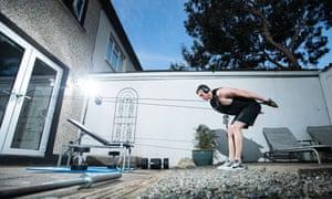 Irish swimmer Brendan Hyland uses his door handles to improvise training at his home in Dublin,