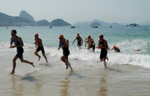 Competitors emerge from the sea after the swim leg in the mens triathlon on Copacabana beach