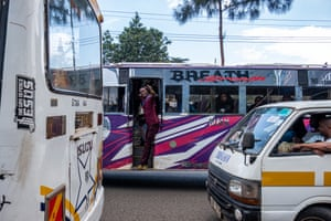A conductor waves from his matatu