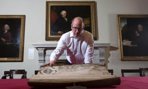 Archivist Mark Pomeroy with the charter for the Society of Artists of Great Britain and its roll of obligation