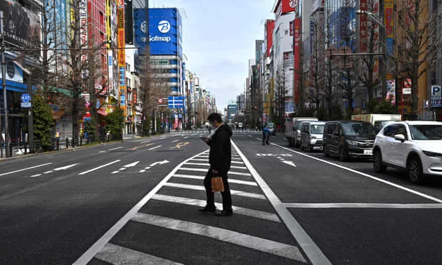A man wearing a face mask, amid concerns of the Covid-19 coronavirus, crosses a street in the Akihabara district in Tokyo
